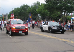 police and fire vehicles leading parade down street