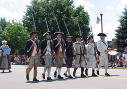 Revolutionary War soldiers marching in parade down street