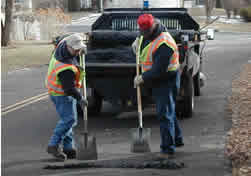 streets workers repairing pothole in street
