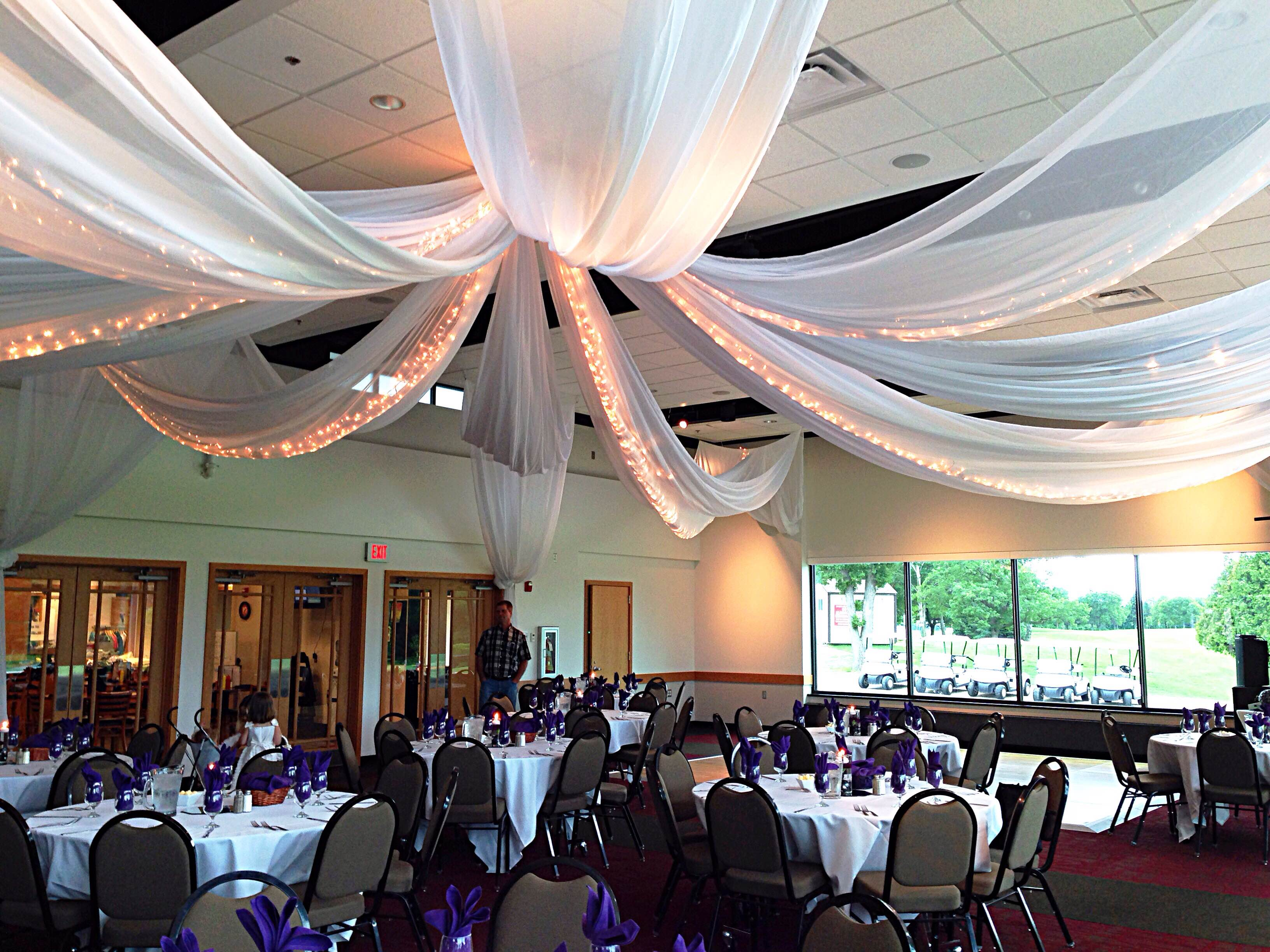 banquet tables with place settings and ceiling draperies
