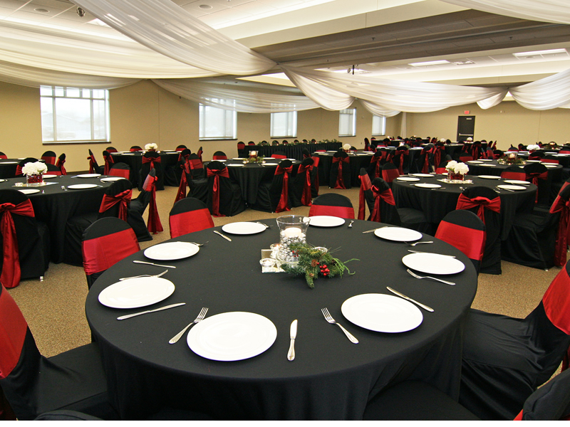 Room set up for banquet with tables, chairs, linens, place settings, and draperies