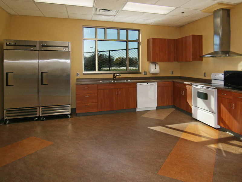 Kitchen facilities with sink, cabinets, stove, and refrigerators